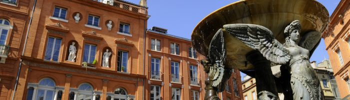 view of French brick buildings and fountain in Toulouse
